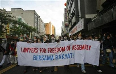 Malaysian lawyers and activists march, before being stopped by police, through the downtown of Kuala Lumpur December 9, 2007. Malaysian police halted an annual human-rights march on Sunday, arresting at least four people and drawing widespread criticism for being intolerant of dissent. (Stringer/Reuters)
