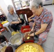 Elderly volunteers peel potatoes at the Singapore Buddhist Lodge